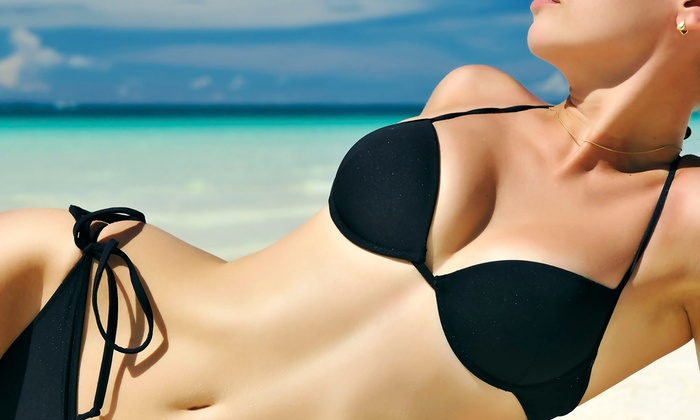 Extreme Tanning - Multiple Locations: 6 or 12 Tanning Sessions in a Heartland 128 Bed, or Two UV Free Mystic Tan Spray Tans at Extreme Tanning (Up to 75% Off)