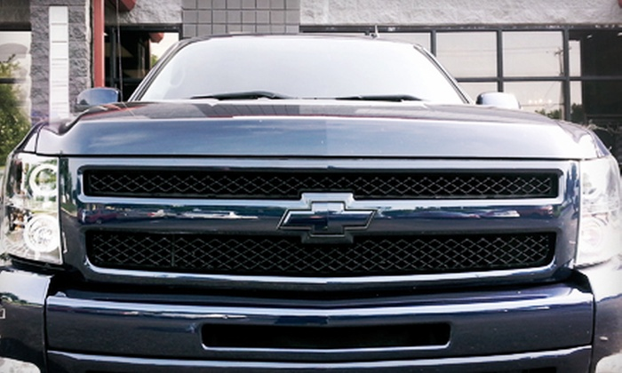The Tint Guy, LLC - Saint Charles: Two Custom Chevrolet Badges or a CarbonXP Window-Tinting Package with Sun Strip at The Tint Guy, LLC (Up to Half Off)