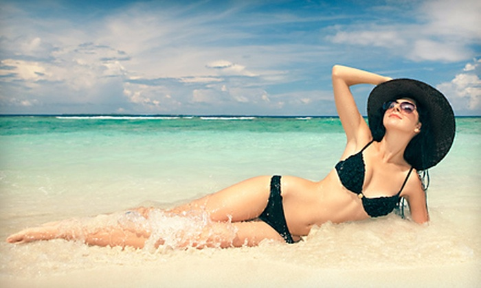Exotic Tans - Multiple Locations: Month of Unlimited UV Tanning, One Teeth-Whitening Treatment, and Two or Five Spray Tans at Exotic Tans (Up to 69% Off)