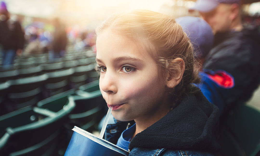 Girl drinking a beverage at a baseball game