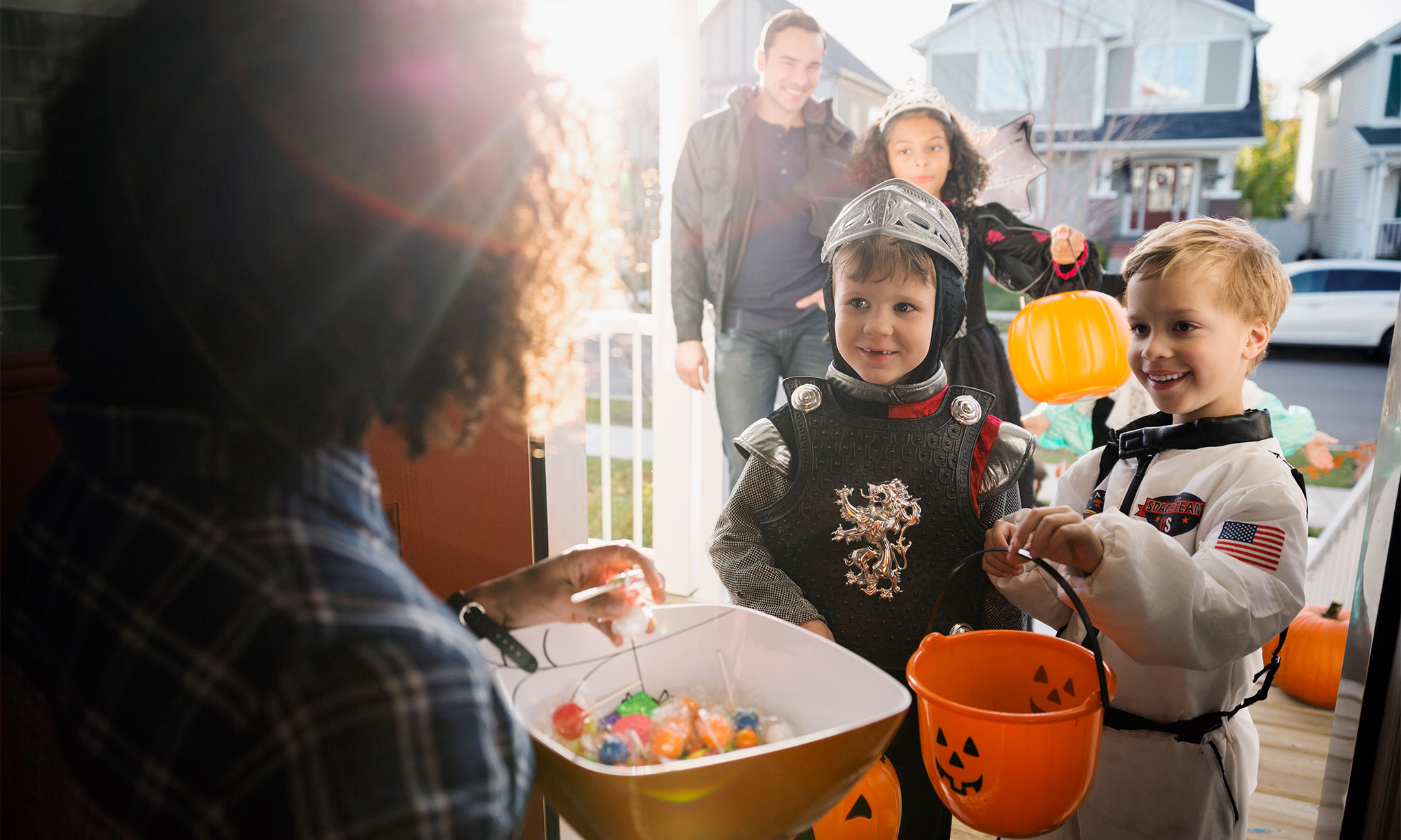 Little boy trick-or-treaters receiving candy
