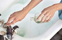 woman-adding-essential-oil-to-a-bath