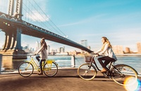 Two women biking near NYC bridge