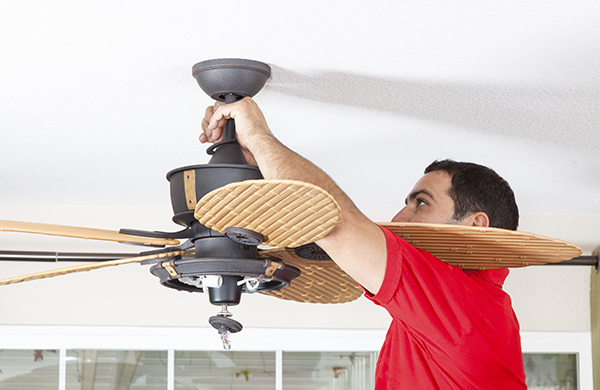 brunette man installing hanging ceiling fan