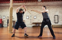 two people in sword fighting class