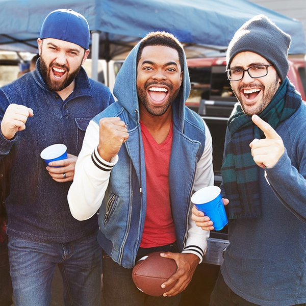 Three male friends cheering at a tailgate