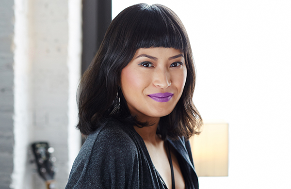 olive-skinned woman with bangs and bold purple lipstick