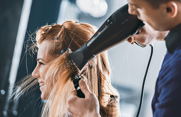 woman getting a blowout from a stylist