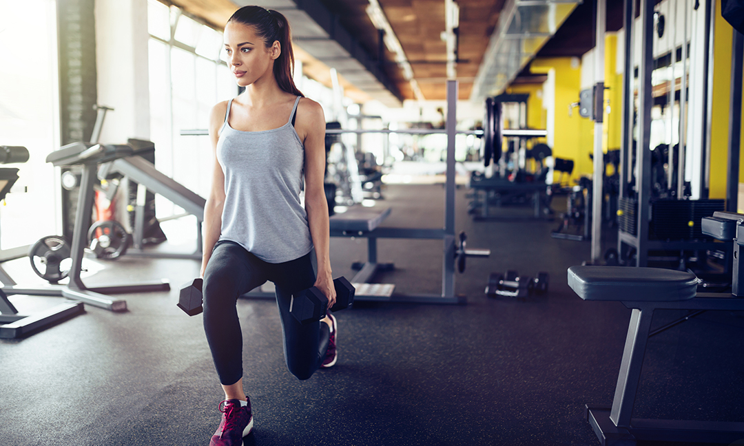woman lifting weights while doing lunges