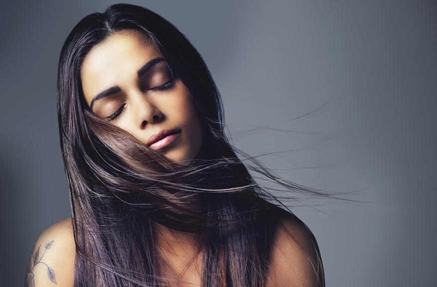woman with straight hair blowing, eyes closed