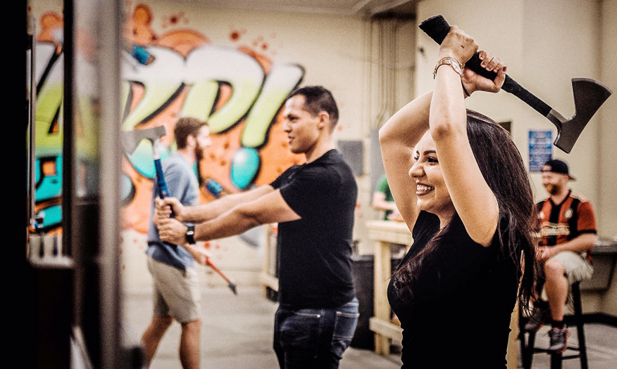 Two people competing in axe throwing