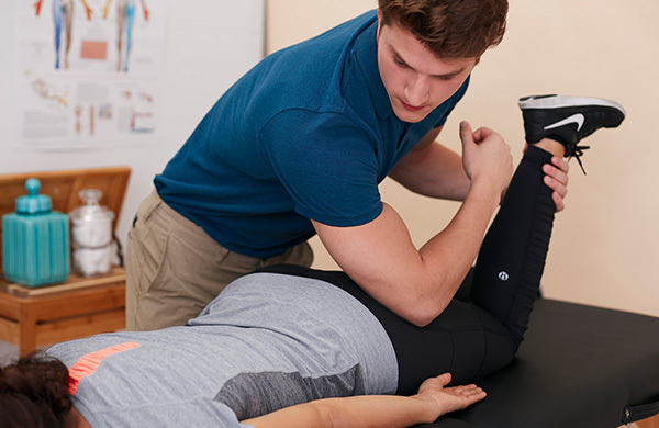 Massage therapist working on woman in workout clothes