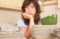 Overwhelmed woman exasperated by pile of neutral colored dishes