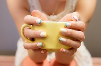 woman with multicolored french mani holding coffee cup