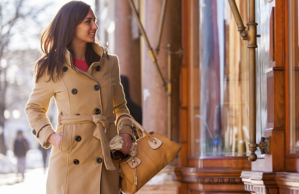 Stylish brunette woman in trench coat holding bowling style handbag