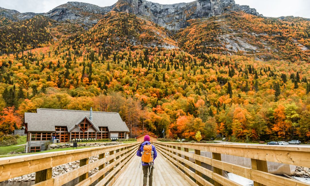 Woman crossing bridge toward mountains in the fall
