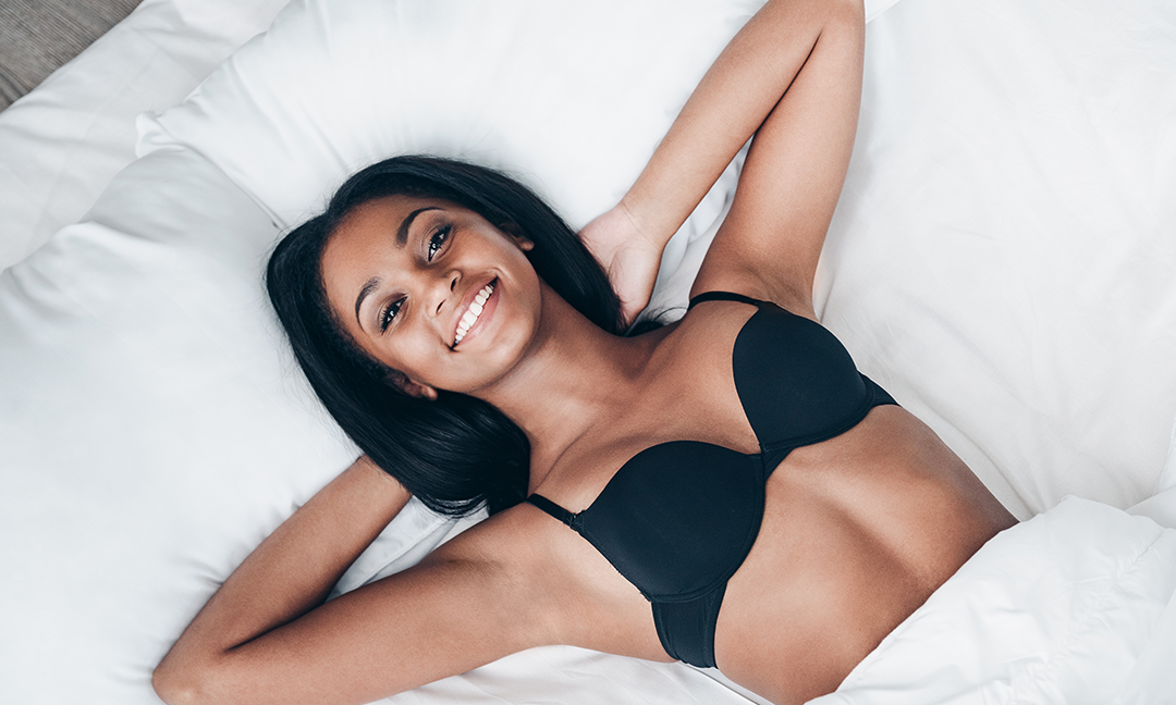 Woman wearing bra laying in bed