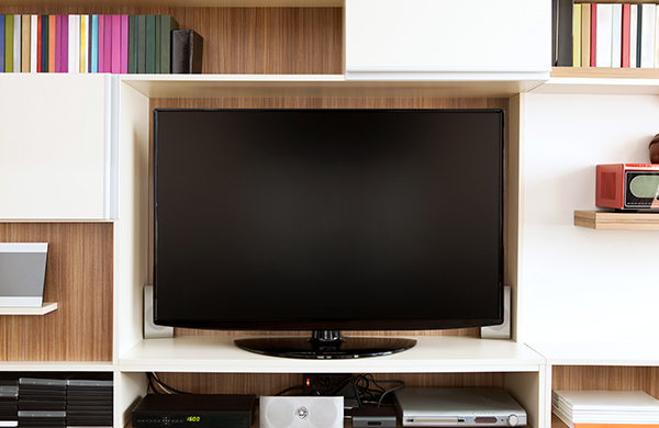 flat screen television mounted in media center cabinet with dvds and media players