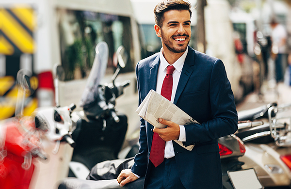 smiling man in suit standing by motorcycles