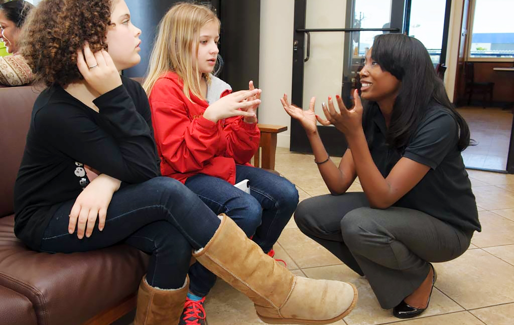 Kneeling Aisha Bowe talks to two sitting girls