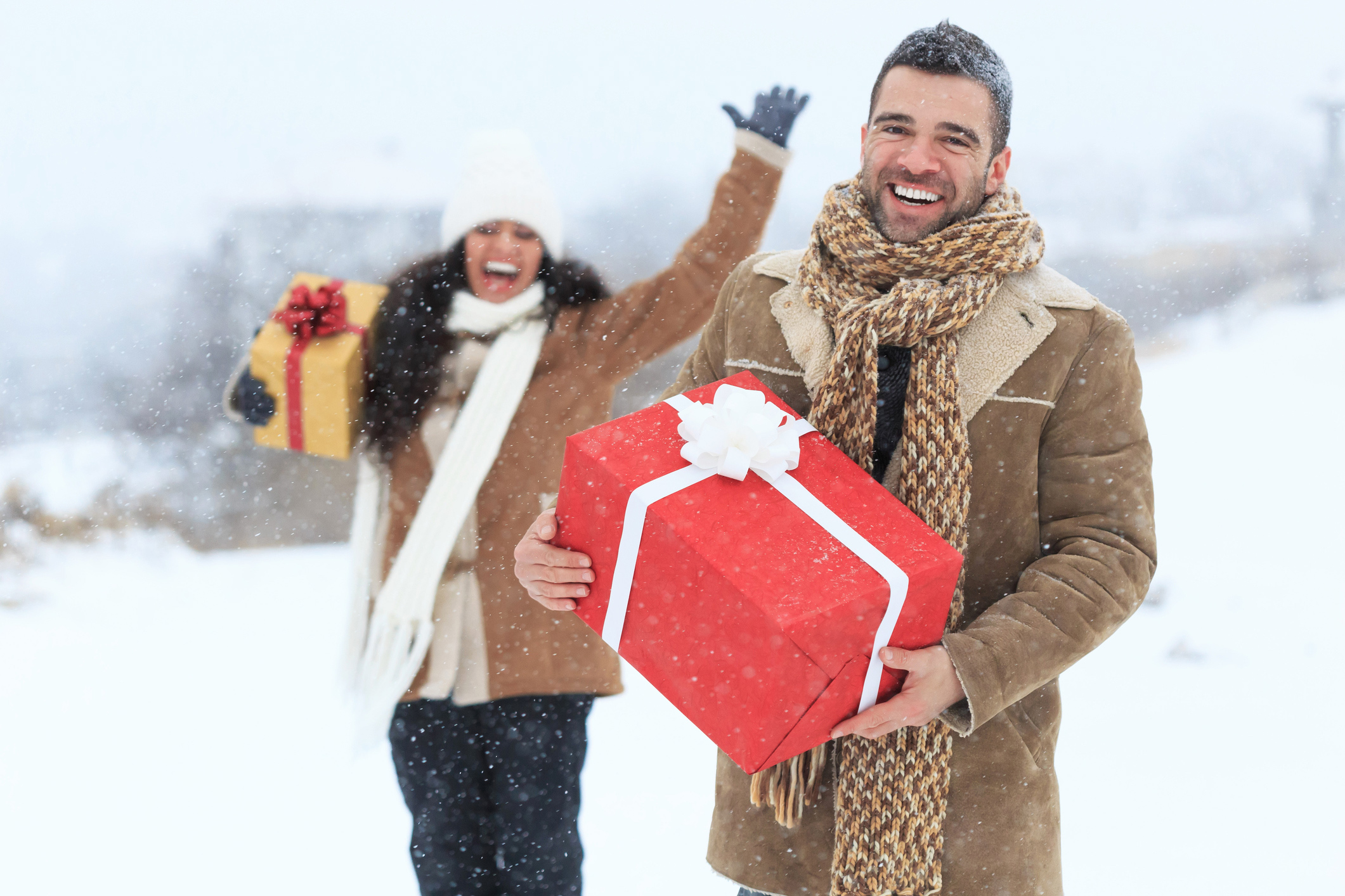 Cheerful man and woman carrying presents in snow
