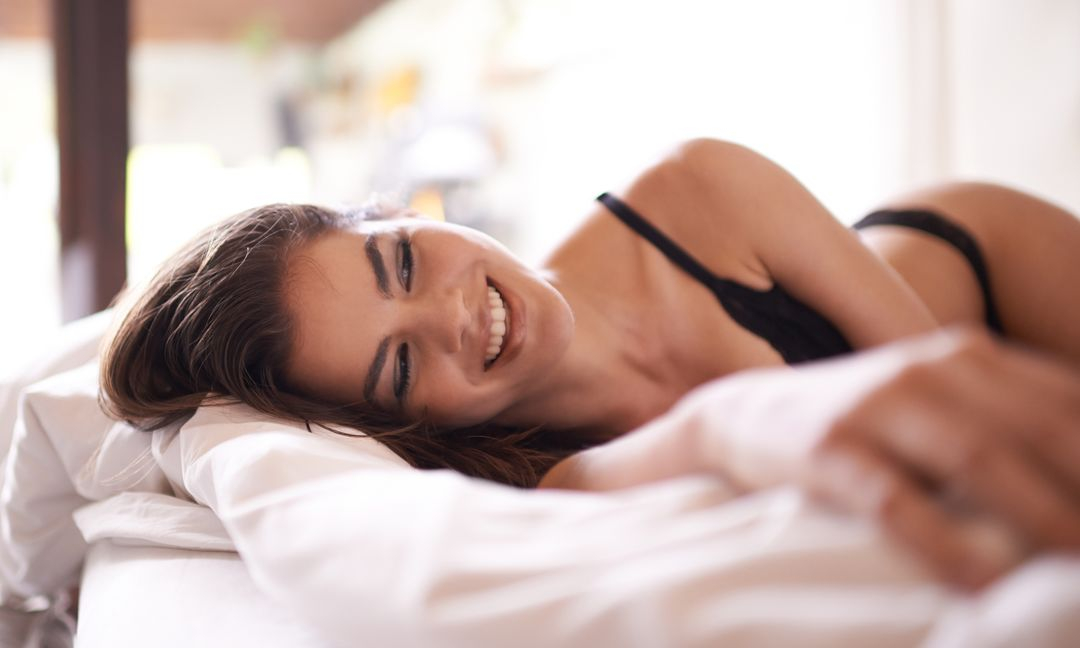 young woman lounging in bed