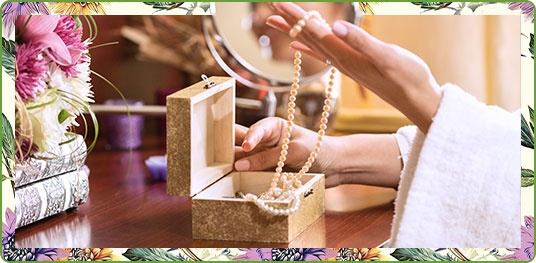 Woman pulling pearl necklace out of jewelry box