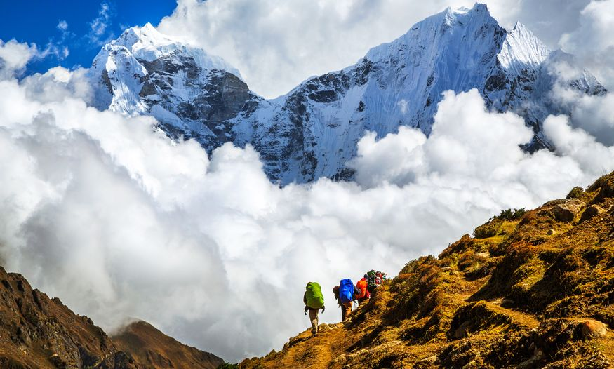 Group of people hiking through Himalayas amid big clouds