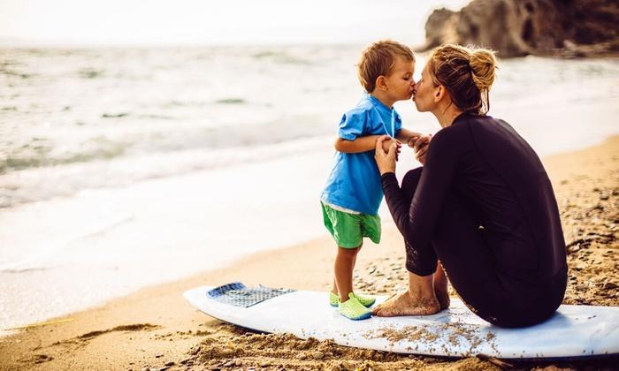 Surfer mom kissing small son