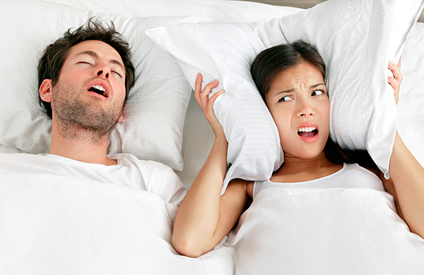 Man snoring in bed with annoyed wife girlfriend