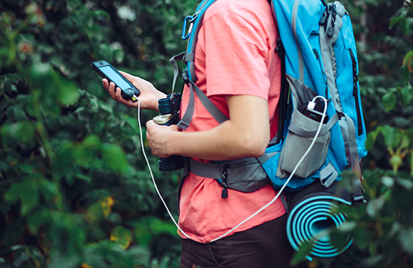man using charging phone while hiking