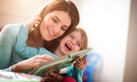 mother reading and laughing with young daughter