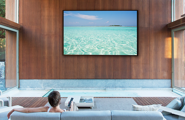woman on living room sofa watching giant wall-mounted flat screen television