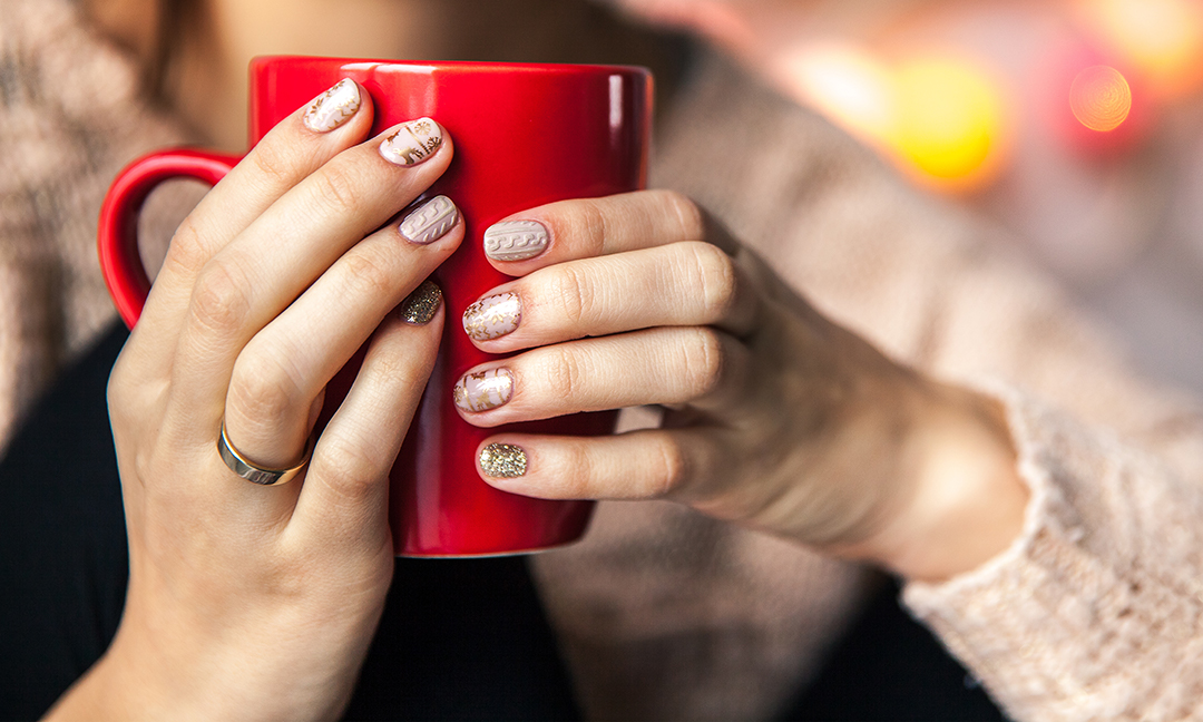 woman with winter nails designs holding mug