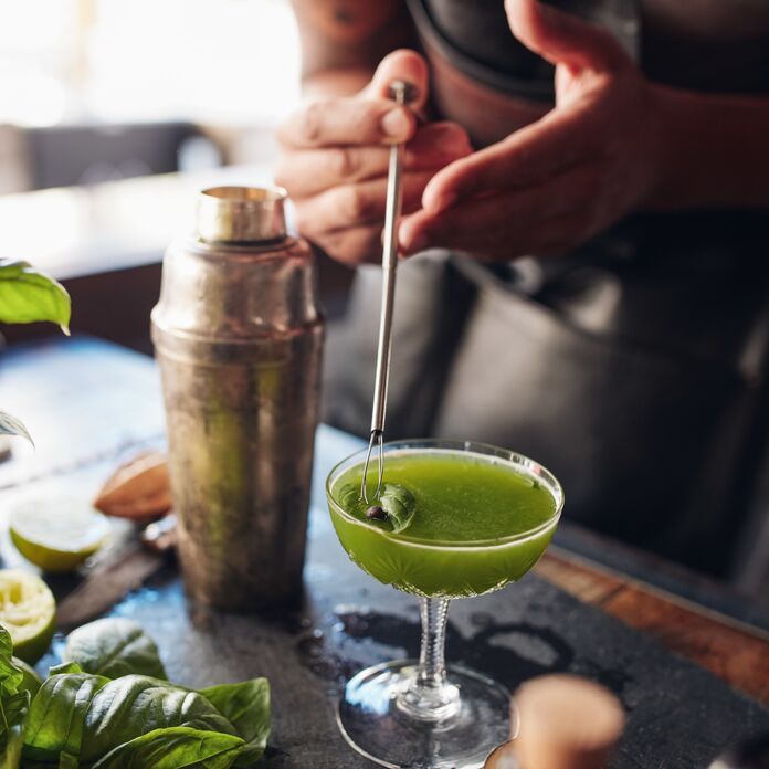 man making a green cocktail