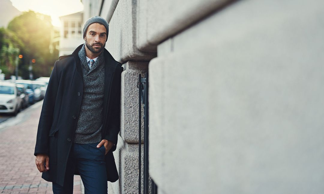 man in sweater and coat leaning against building wall