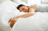 woman smiling lying face-down on mattress