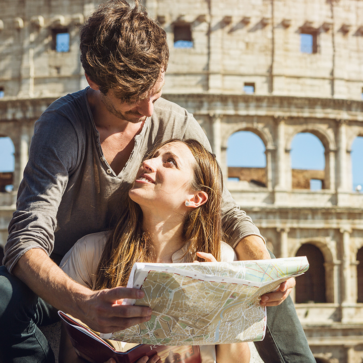 tourist couple looking at eachother over a map in Italy.