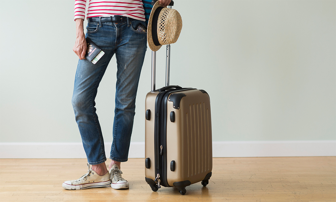 Woman with suitcase and hat ready for a trip