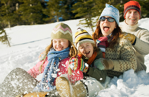 Happy Family Sledding Outdoors in Winter