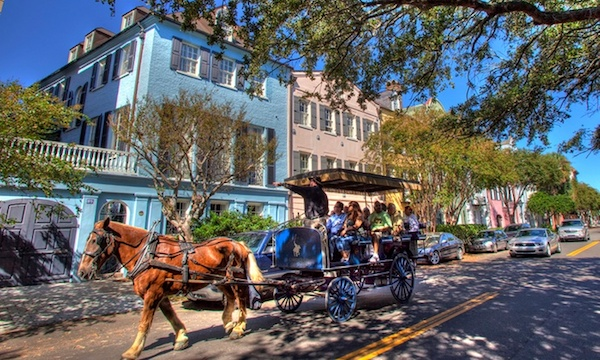 Horse carriage with tourists headed down street