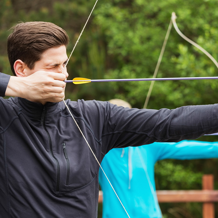 Man taking archery lessons