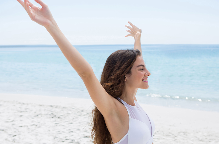 Woman happy on beach with arms over her head