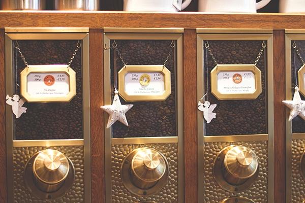 Nahaufnahme der Kaffeeschütten im Holzregal im Gliss Caffee Contor in Köln