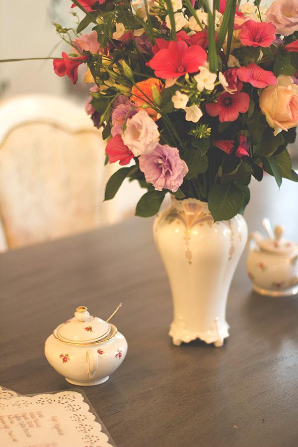 großer Tisch mit frischem Blumenstrauß und altem Geschirr im Café Miss Päpki im belgischen Viertel in Köln