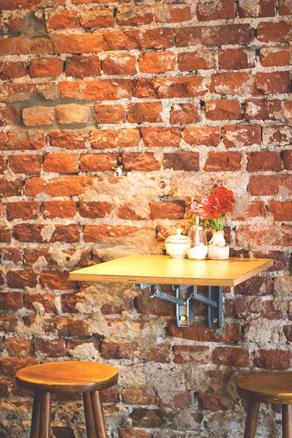 Die freigelegte Backsteinwand und Sitzmöglichkeiten im Café Rotkehlchen in Köln-Ehrenfeld