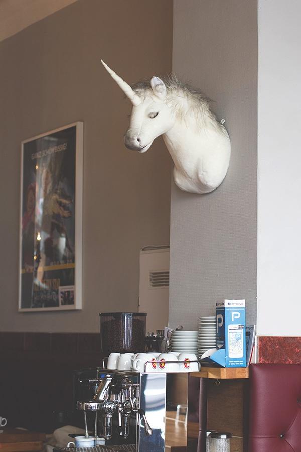 Blick auf die Espressomaschine und den Einhornkopf an der Wand