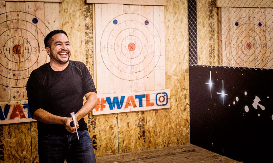 Man laughing after throwing an axe