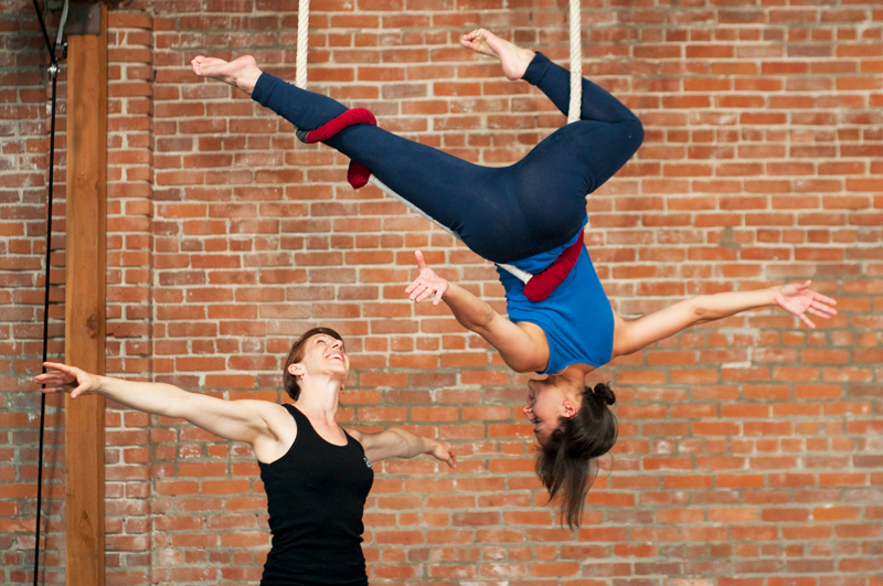 Woman teaching student to do acrobatics with silks