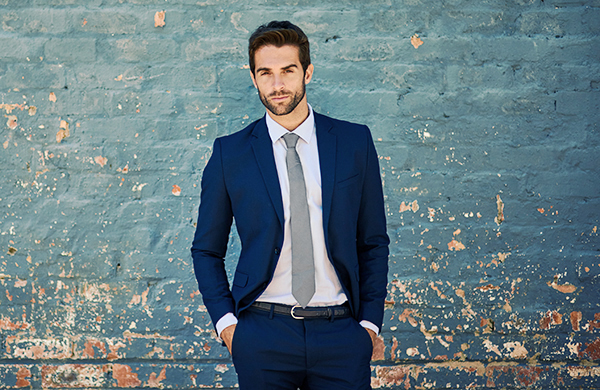 suit style color man in blue suit near brick wall